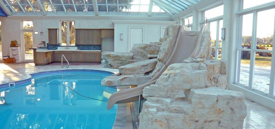 Indoor pool and solarium with a slide inside some decorative rock