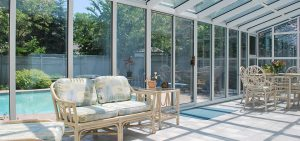 sunny room looking outwards to a summer day with a blue pool